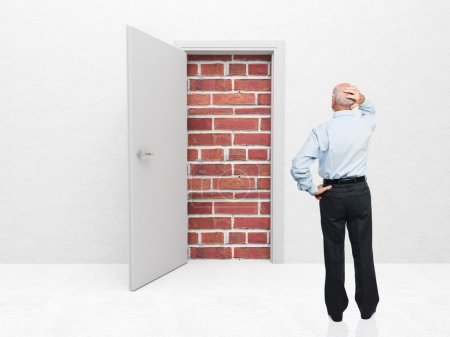 Photo for Standing old man and door with brick wall - Royalty Free Image