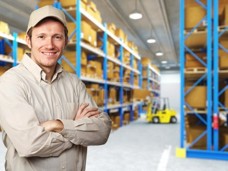 Photo for Smiling delivery man in warehouse - Royalty Free Image