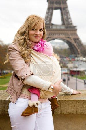 Photo pour Voyager avec bébé. Belle jeune mère avec sa petite fille en fronde à Paris - image libre de droit