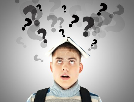Photo for Stressed student with question marks over his head - Royalty Free Image
