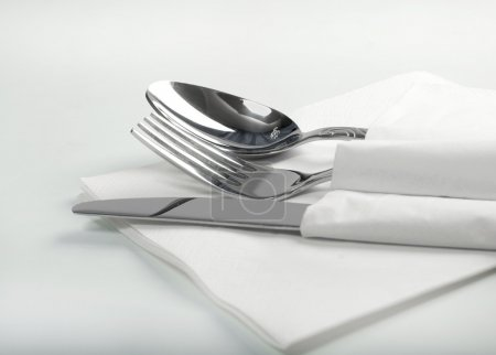 Photo for Spoon, fork and a knife lie on serviette.on a white background - Royalty Free Image