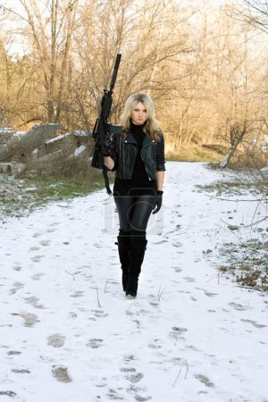Beautiful young blonde with a gun