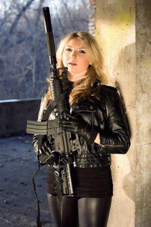 Photo pour Chaude jeune femme en veste de cuir, tenant un fusil - image libre de droit