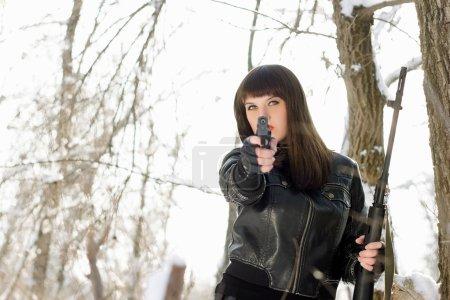Photo pour Portrait d'une magnifique jeune femme avec un pistolet et un fusil - image libre de droit
