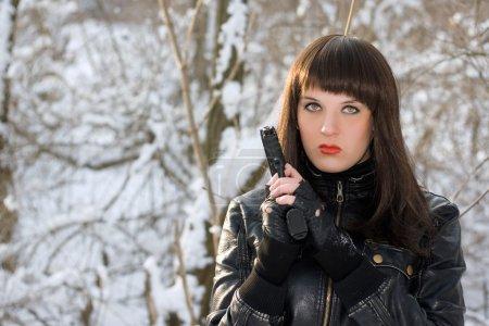Photo pour Portrait de jeune femme avec un pistolet dans la forêt d'hiver - image libre de droit