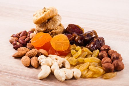 Photo for Dried fruits and nuts heaps on wooden table - Royalty Free Image