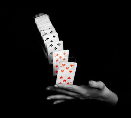 Photo pour Magicien montrant son tour avec des cartes sur fond noir - image libre de droit