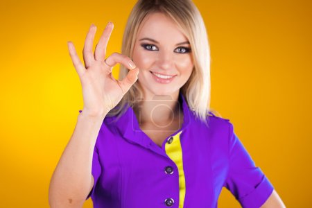 Photo for Beautiful young business woman showing okay on yellow background - Royalty Free Image