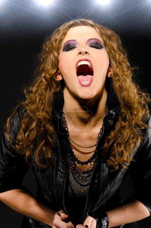 Photo pour Femme chante chanson rock sur fond foncé - image libre de droit