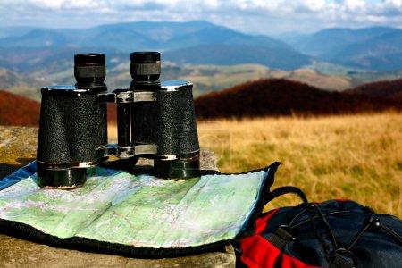 Photo pour Une image de jumelles et une carte sur herbe sèche. Thème aventure - image libre de droit
