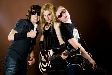 Photo pour Groupe de rock jouant dans photostudio sur fond marron - image libre de droit