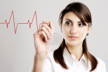 Photo for An image of young doctor drawing cardiogram in air - Royalty Free Image