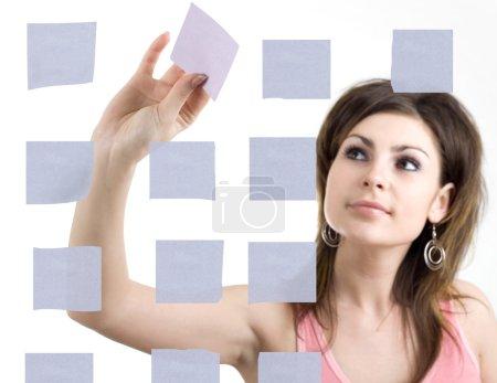 Photo pour Une fille collant des notes sur le mur - image libre de droit