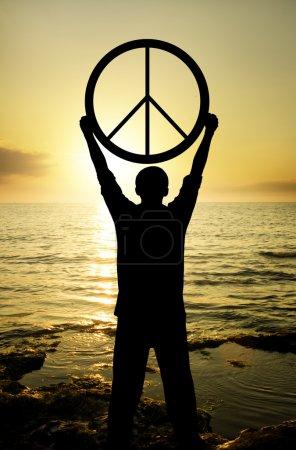 Photo pour Homme en attente du coucher du soleil le signe de la paix - image libre de droit