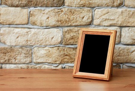 Old photo frame on the wooden table...