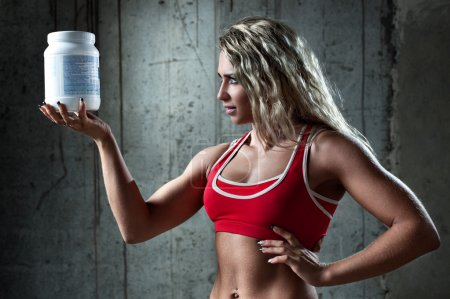 Photo for Young muscular woman with sports nutrition. - Royalty Free Image