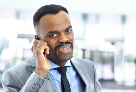 Attractive smiling Afro-American young businessman on phone in office