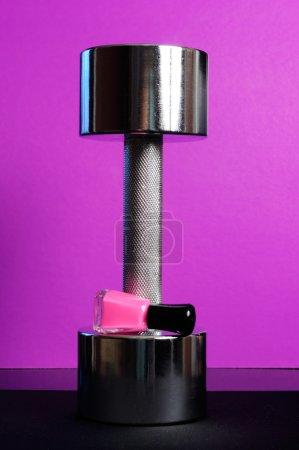 Photo pour Un haltère brillant avec une bouteille de vernis à ongles rose sur fond violet - image libre de droit