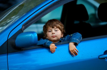 Photo pour Heureux enfant assis dans la voiture - image libre de droit