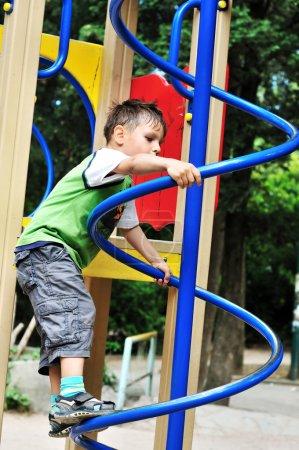 Photo pour Petit garçon actif grimpant sur l'aire de jeux - image libre de droit