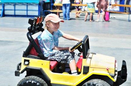 Photo pour Petit garçon conduisant une voiture dans le centre-ville - image libre de droit
