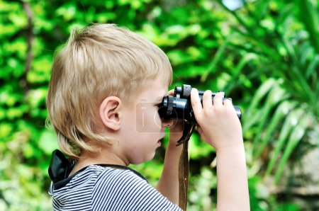 Photo for Boy looking through binocular in selective focus - Royalty Free Image
