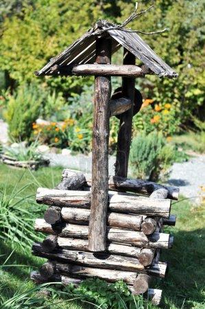 Photo pour Village vieux puits en bois dans le jardin - image libre de droit