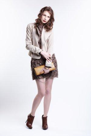 Photo pour Portrait complet de belle jeune femme brune en veste, robe et bottes avec embrayage à la main sur gris - image libre de droit