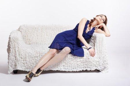 Photo pour Portrait complet de belle jeune femme brune en robe bleue et chaussures de cour relaxantes sur canapé - image libre de droit