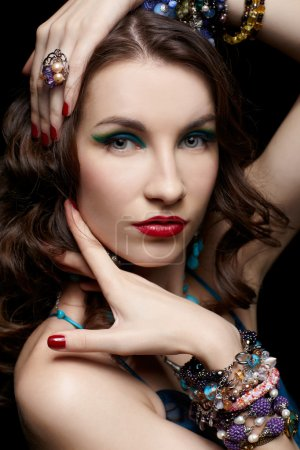 Photo for Portrait of young beautiful brunette woman in jewelry on black - Royalty Free Image