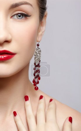 Photo for Close-up portrait of young beautiful brunette woman in ear-rings touching her shoulder with manicured fingers - Royalty Free Image