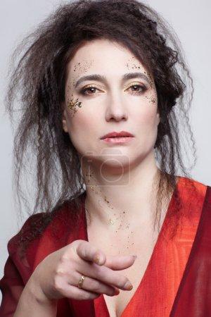 Photo pour Brunette femme en robe de chambre rouge pointant du doigt - image libre de droit
