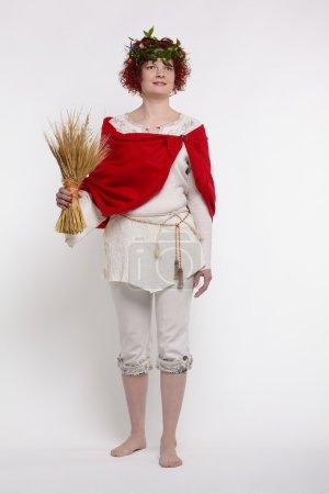 Photo pour Portrait complet de femme rousse esclave moissonneuse dans des vêtements russes traditionnels et guirlande de fleurs avec une gerbe de blé à la main - image libre de droit