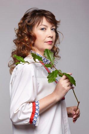 Photo pour Portrait complet de femme rousse esclave avec branche de chêne dans des vêtements russes traditionnels - image libre de droit