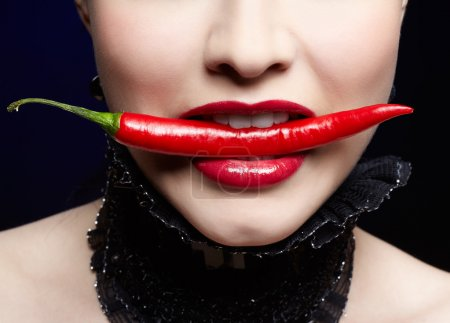 Photo for Close-up portrait of beautiful girl's lower part of face in black lacy collar biting spicy hot red cayenne - Royalty Free Image