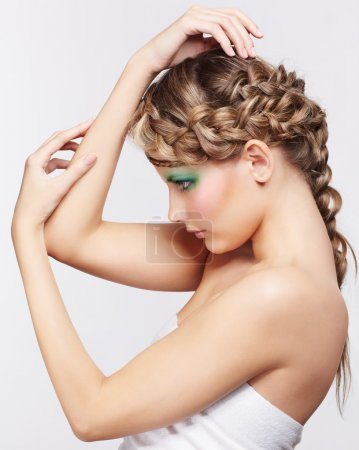 Photo for Sideview portrait of beautiful young dark blonde woman with creative braid hairdo posing on gray - Royalty Free Image