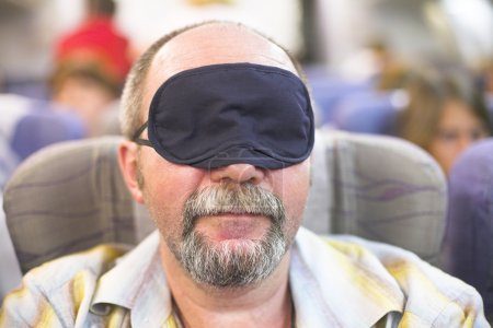 Photo for Manture man in sleeping mask in the airplane - Royalty Free Image