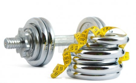 Photo for Dumbbell with a measuring tape on white background - Royalty Free Image