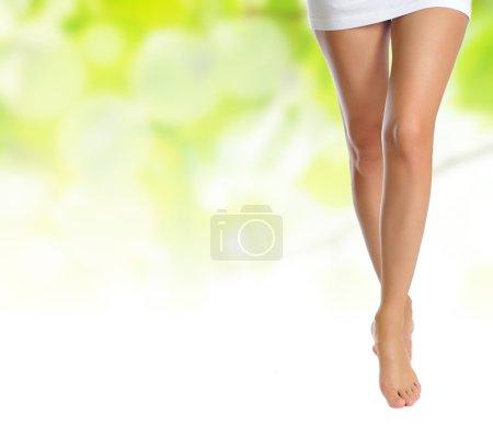 Photo pour Sexy jambes femmes minces nues faisant étape sur fond naturel vert - image libre de droit