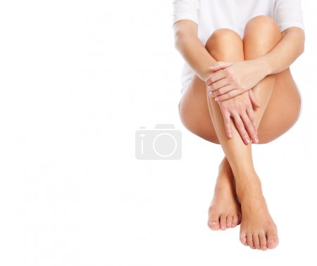 Cut out slender naked female legs being massaged isolated on whi