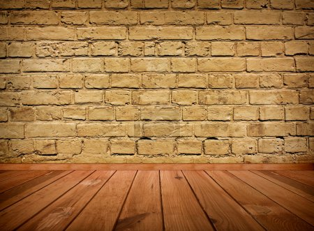Vintage brown grungy textured brick interior with wooden floor