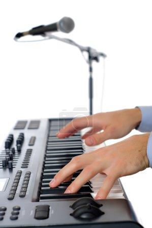 Photo pour Maicrophone et les mains masculines jouant du piano dans le studio isolé sur blanc pepth peu profond de firld avec accent plissé sur la main - image libre de droit