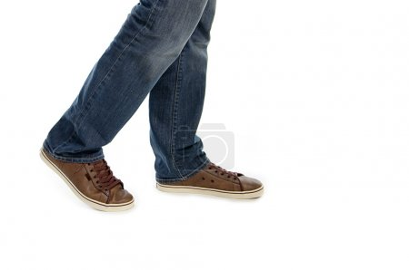 Male legs in jeans and brown sneakers shoes