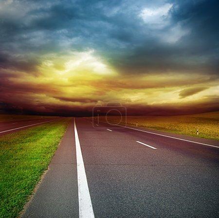 Route asphaltée dans le champ au-dessus du ciel orageux