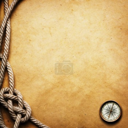 Old compass and rope on grunge background...