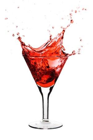 Foto de Martini rojo se vierte en un vaso de martini, aislado sobre un fondo blanco - Imagen libre de derechos