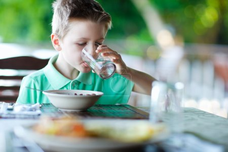 Photo for Cute little boy at restaurant drinking water - Royalty Free Image