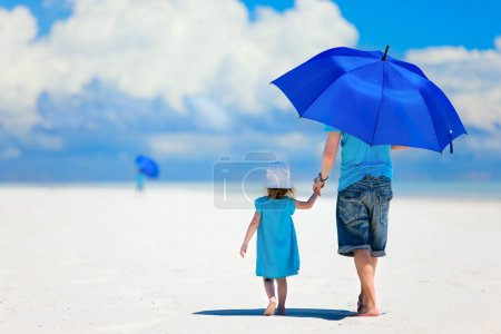 Photo for Father and daughter at beach with umbrella to hide from sun - Royalty Free Image