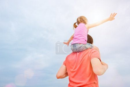 Father carrying his daughter on shoulders