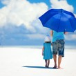 Father and daughter at beach with umbrella to hide...